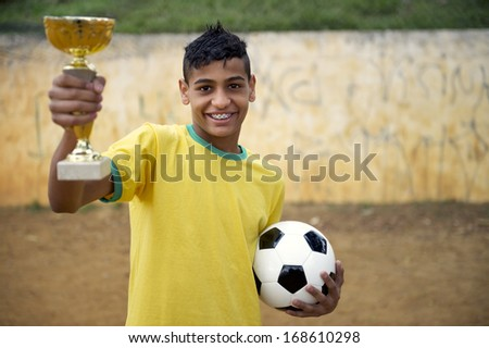 Smiling young Brazilian football player holding trophy and soccer ball on basic dirt football pitch - stock photo