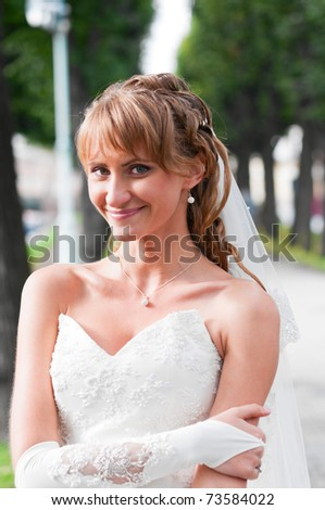 smiling young bride is standing in city park