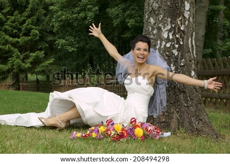 Smiling young bride sitting under tree with arms outstretched - stock photo