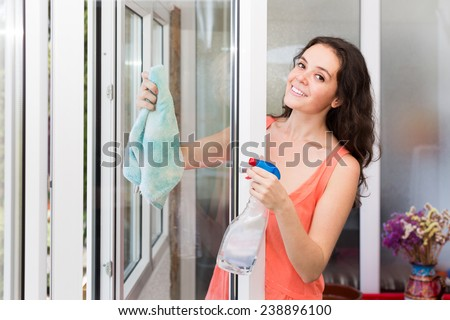 Smiling young brunette cleaning windows using atomizer indoor  - stock photo