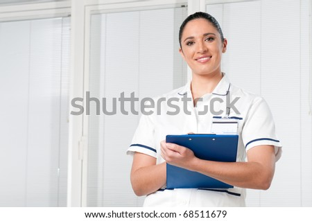 Smiling young brunette female nurse looking at camera at hospital