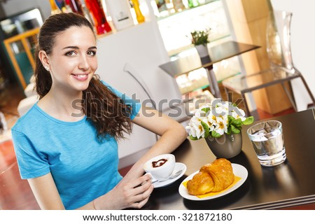 Smiling Young brunette girl at the bar having a coffee break with heart shaped cappuccino - stock photo