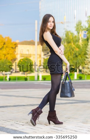 Smiling young brunette wearing black dress posing with handbag - stock photo