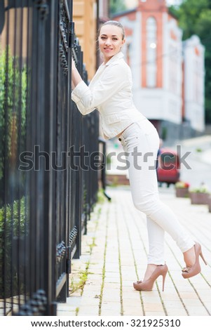 Smiling young brunette wearing white pants and jacket posing near metal fence - stock photo