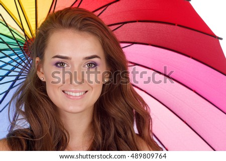 Smiling young brunette woman in white blouse with multi-coloured umbrella