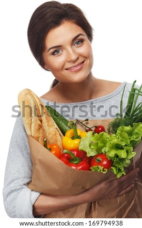 Smiling young brunette woman with grocery bag full of fresh vegetables
