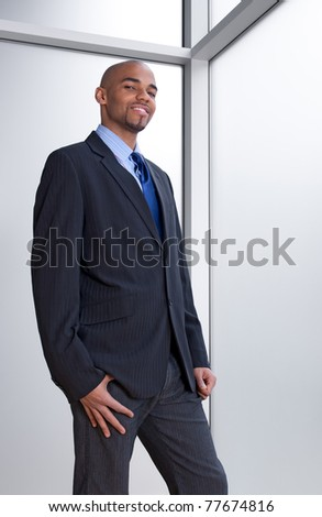 Smiling young business man beside an office window. - stock photo