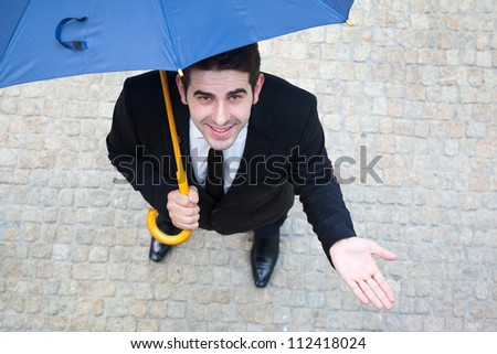 Smiling young business man checking if it's raining - stock photo