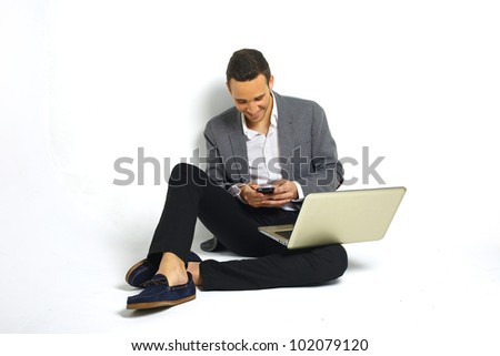 smiling young business man with a laptop sitting at floor sending sms with a smart phone