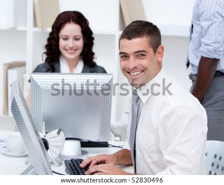 Smiling young business people working at computers in the office - stock photo
