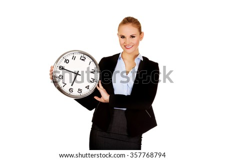 Smiling young business woman holding office clock. - stock photo