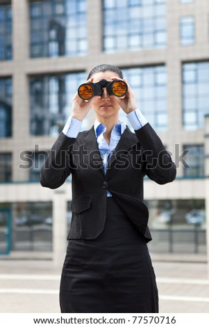 smiling young business woman looking through the binoculars in front an office building - stock photo