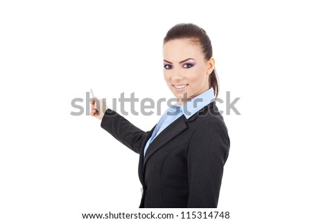 smiling young business woman presenting something in the back with a pen in her hand and looking at the camera. Isolated over white background