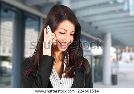 Smiling young business woman talking at the phone - stock photo