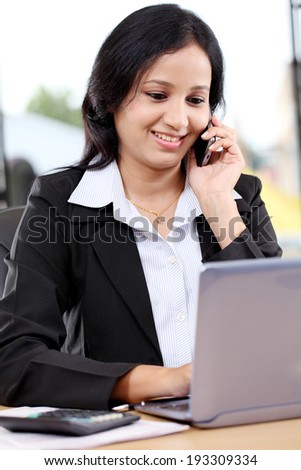 Smiling young business woman talking on mobile phone at office