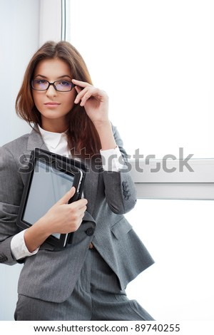 Smiling young business woman using tablet PC while standing relaxed near window at her office - stock photo