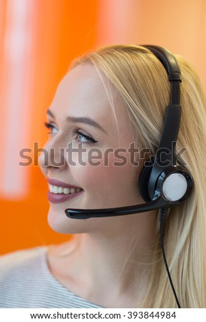Smiling young business woman wearing a headset answering calls at a client service centre or wanting to communicate hands free while continuing to work in her office - stock photo