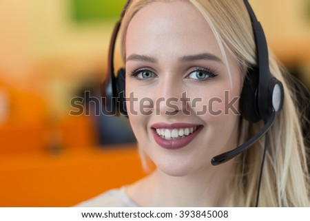 Smiling young business woman wearing a headset answering calls at a client service centre or wanting to communicate hands free while continuing to work in her office