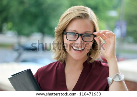Smiling Young Business Woman Wearing Eye Glasses Looking at the Camera - stock photo