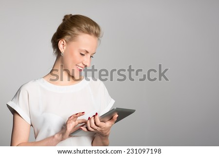 Smiling young business woman with a tablet PC. Gray wall. - stock photo
