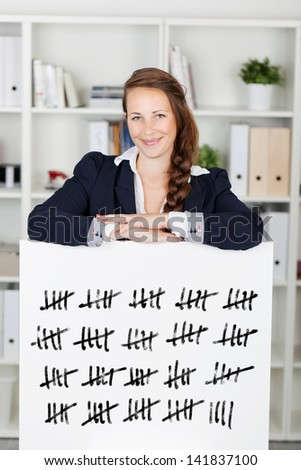 Smiling young business woman with her arms resting on a tally card counting in batches of five struck through with a line - stock photo
