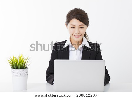 smiling young business woman working with  laptop and green plant