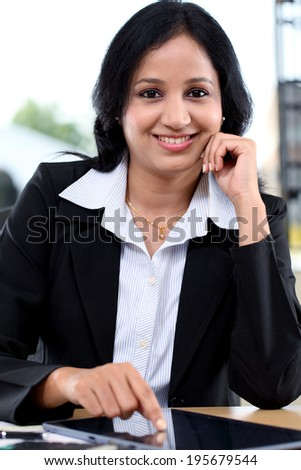 Smiling young business woman working with tablet computer at office
