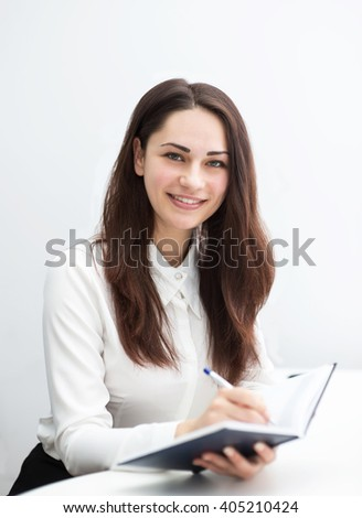 smiling young business woman writes notes in diary - stock photo