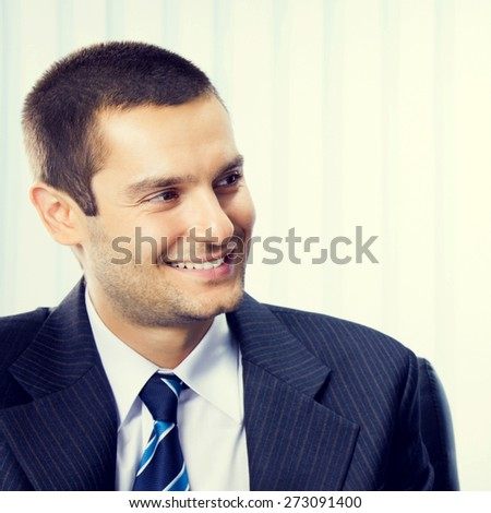 Smiling young businessman at office - stock photo
