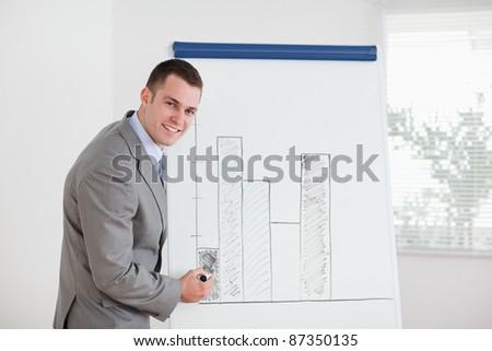 Smiling young businessman editing column graph - stock photo