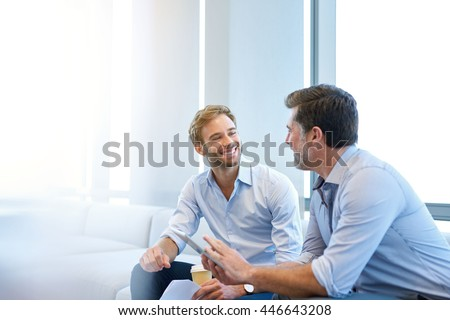 Smiling young businessman enjoying a positive conversation with a mature business partner in a modern space with large windows - stock photo