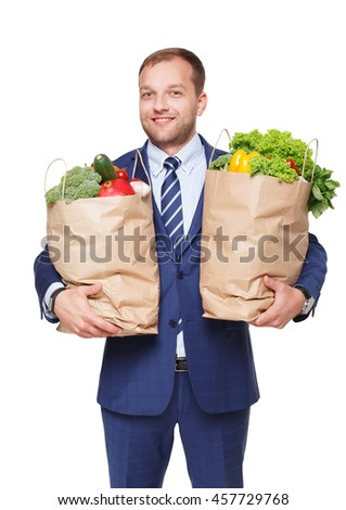 Smiling young businessman hold shopping bags full of groceries isolated at white background. Healthy food shopping. Paper package with vegetables and fruits, happy man buyer show thumb up - stock photo