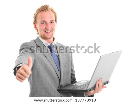 Smiling young businessman holding a computer doing thumbs up. Wearing a grey suit with a blue tie. White background.