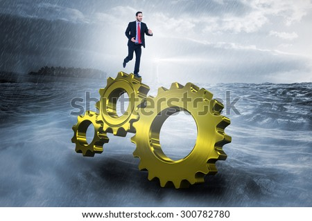 Smiling young businessman in suit running against stormy sea with lighthouse - stock photo