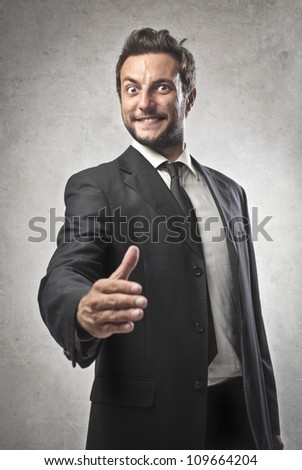 Smiling young businessman lending his hand - stock photo
