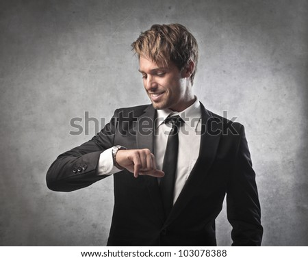 Smiling young businessman looking at his wristwatch - stock photo