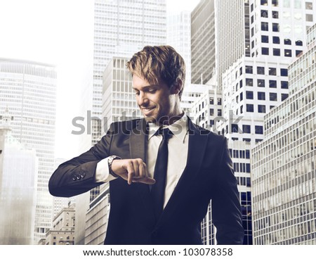 Smiling young businessman looking at his wristwatch with cityscape in the background - stock photo