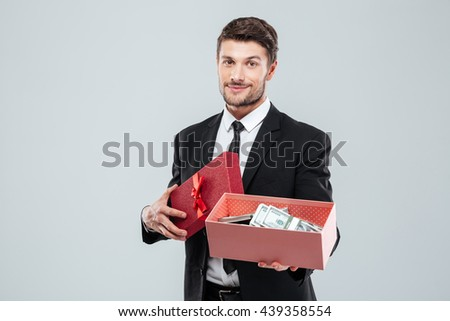 Smiling young businessman showing present box full of money over white background - stock photo
