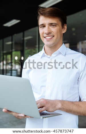 Smiling young businessman standing and working with laptop
