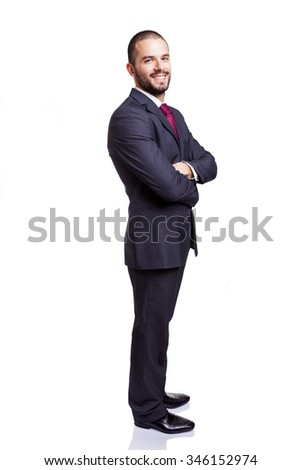 Smiling young businessman standing with arms crossed on white background - stock photo