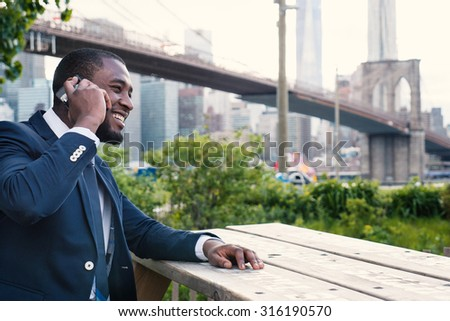 Smiling young businessman talking at the phone. Brooklyn Bridge on the background, New York City. - stock photo