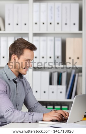 Smiling young businessman using laptop at office desk - stock photo