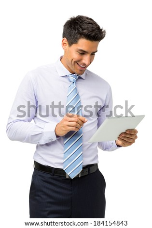 Smiling young businessman using tablet computer against white background. Vertical shot.