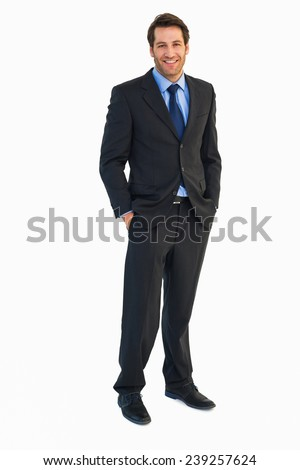 Smiling young businessman with hands in pockets on white background - stock photo