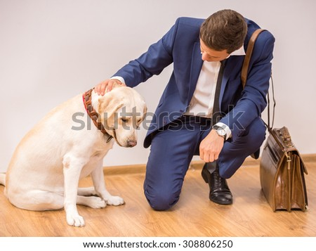 Smiling young businessman with his dog sitting on floor. - stock photo
