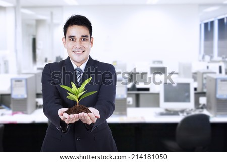 Smiling young businessman with small plant in his hands - stock photo