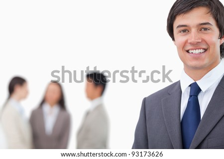 Smiling young businessman with team behind him against a white background