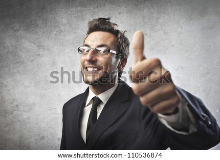 Smiling young businessman with thumbs up - stock photo