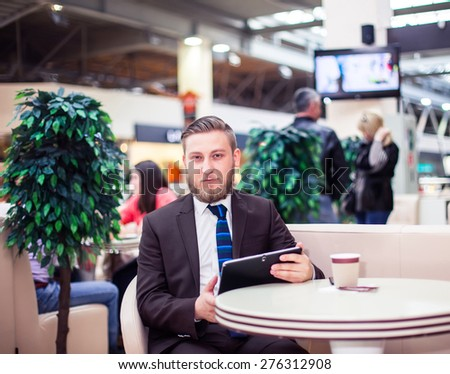 Smiling young businessman with touchpad and coffee - stock photo