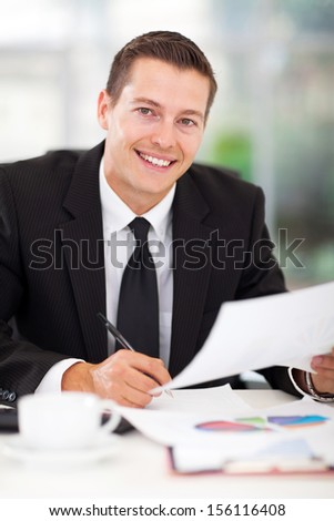 smiling young businessman working in office - stock photo
